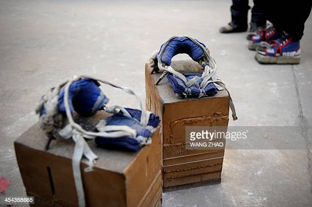 WITH 'CHINAHEALTHOFFBEAT' BY This picture taken on November 15 2013 shows a pair of Zhang Fuxing's iron shoes at a residential district in Tangshan...