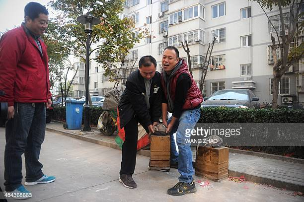 WITH 'CHINAHEALTHOFFBEAT' BY This picture taken on November 15 2013 shows two men lifting up a pair of Zhang Fuxing's iron shoes at a residential...
