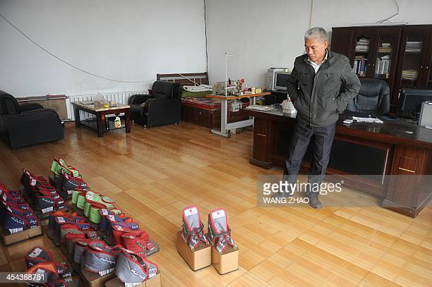 WITH 'CHINAHEALTHOFFBEAT' BY This picture taken on November 15 2013 shows Zhang Fuxing looking at his iron shoes at his office in Tangshan in...