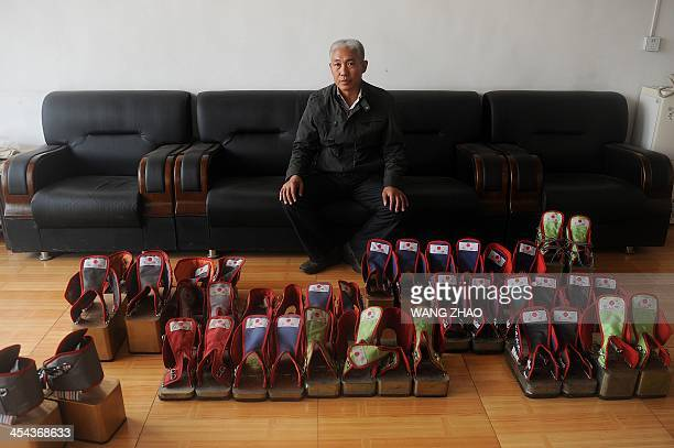 WITH 'CHINAHEALTHOFFBEAT' BY This picture taken on November 15 2013 shows Zhang Fuxing posing for a photo with his iron shoes at his office in...
