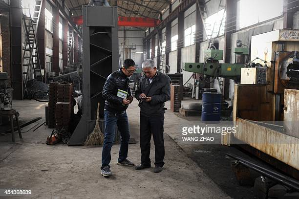 WITH 'CHINAHEALTHOFFBEAT' BY This picture taken on November 15 2013 shows Zhang Fuxing talking with his son at his factory in Tangshan in northern...