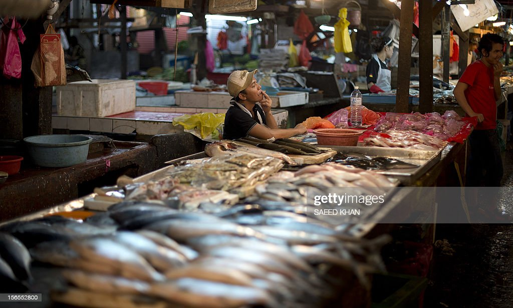 This picture taken on November 16, 2012 shows a vendor smoking a cigarette while waiting for customers at his fish stall in down town Kuala Lumpur. Malaysia's economy grew a better-than-expected 5.2 percent in the third quarter as domestic demand continued to compensate for a slowdown in exports. The central bank said Southeast Asia's third-largest economy expanded due to private consumption and private and public investment in such sectors as transportation, oil and gas, and public utilities. AFP PHOTO / Saeed KHAN