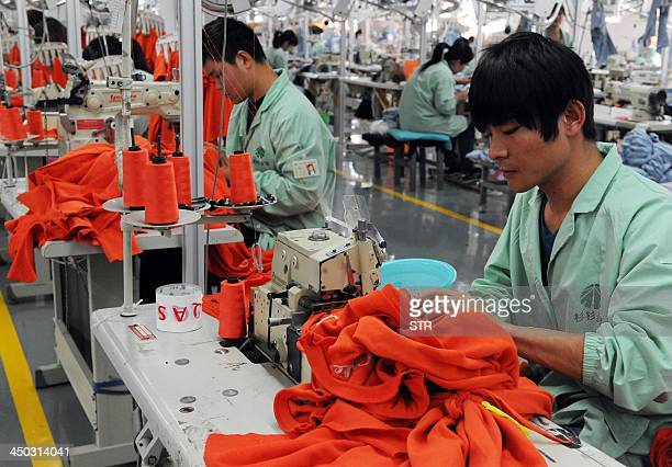 This picture taken on November 16 2013 shows workers sewing in a clothing factory in Bozhou east China's Anhui province China's quick release of a...
