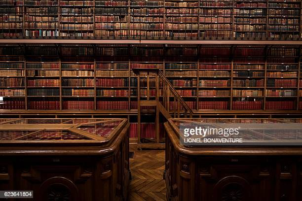 This picture taken on November 16 shows books and a collection of coins inside the library of the Palais du Luxembourg which houses the French Senate...