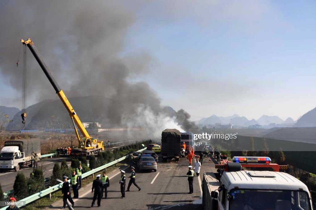 This picture taken on November 17, 2012 shows rescuers putting out a fire after a 69-car traffic accident that resulted in massive fender-benders going in both directions in Shanghai-Kunming highway near Anshun, southwest China's Guizhou province. The accident left nine people dead and 25 injuried, state media reported. CHINA OUT AFP PHOTO