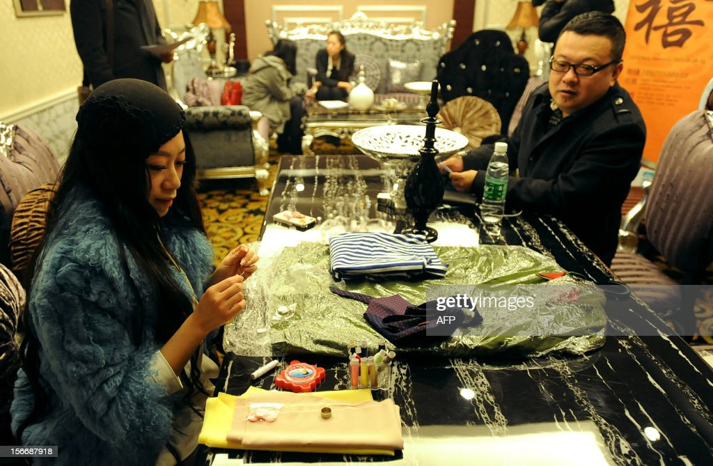 This picture taken on November 18, 2012 shows a woman participant sewing clothes during an interview of a matchmaking event for China's multi-millionaires in Wuhan, central China's Hubei province. This matchmaking event arranged by the China Entrepreneur Club for Singles received the participation of 169 women in Wuhan, while only 5 of them pass all the tests for the first round selection. CHINA