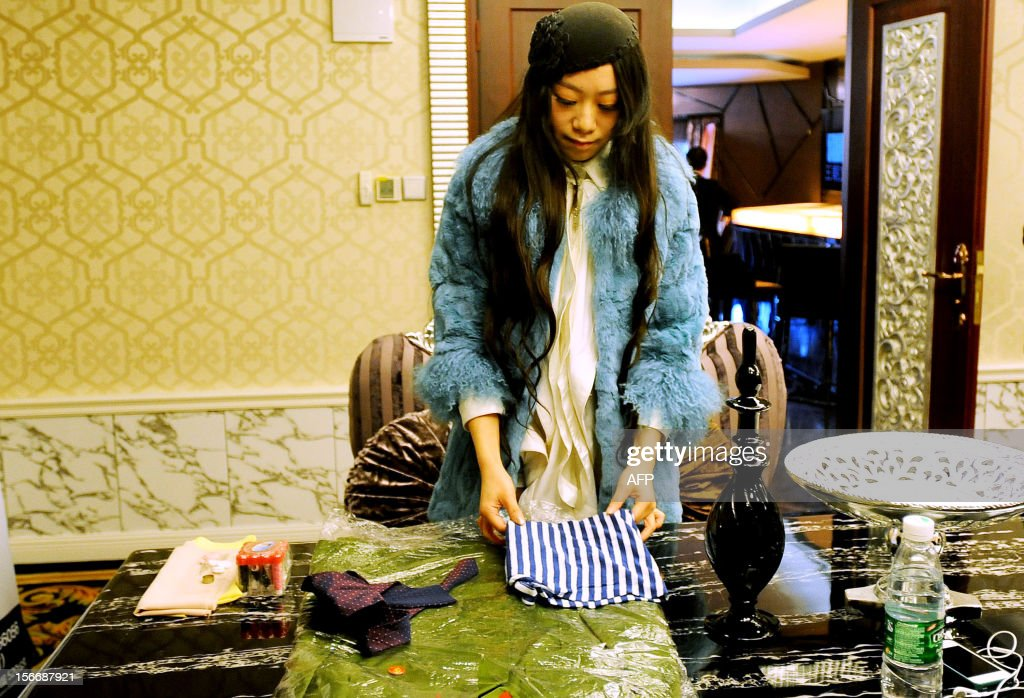 This picture taken on November 18, 2012 shows a woman participant folding clothes during an interview of a matchmaking event for China's multi-millionaires in Wuhan, central China's Hubei province. This matchmaking event arranged by the China Entrepreneur Club for Singles received the participation of 169 women in Wuhan, while only 5 of them pass all the tests for the first round selection. CHINA