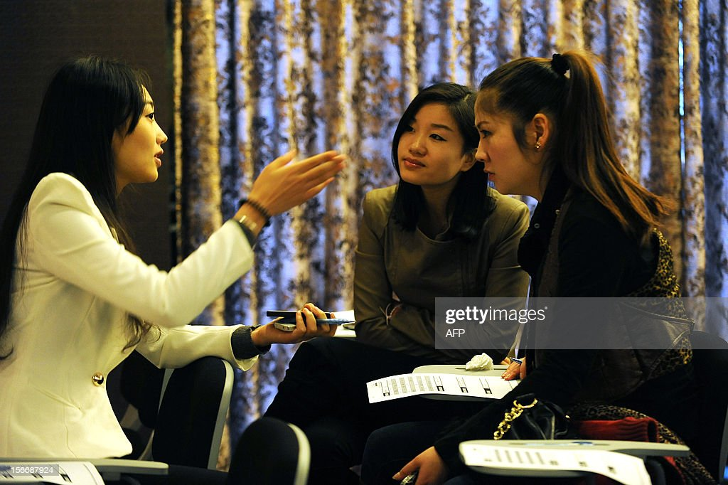 This picture taken on November 18, 2012 shows two woman accepting an interview during a matchmaking event for China's multi-millionaires in Wuhan, central China's Hubei province. This matchmaking event arranged by the China Entrepreneur Club for Singles received the participation of 169 women in Wuhan, while only 5 of them pass all the tests for the first round selection. CHINA