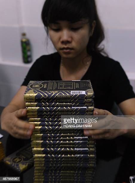 This picture taken on November 18 2013 shows a Vietnamese worker packing a chocolate bar at chocolate workshop Marou Vietnam's first artisan...