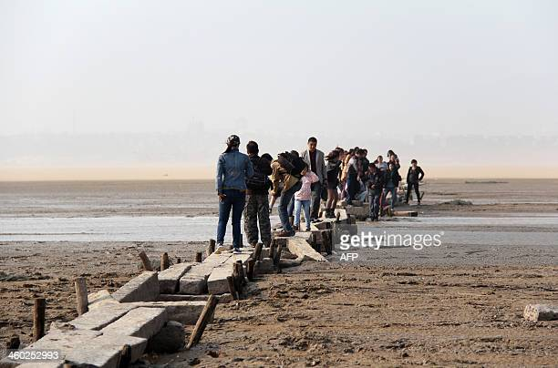 This picture taken on November 2 2013 shows people walking on an ancient stone bridge on the dried up lakebed of Poyang lake in Jiujiang east China's...