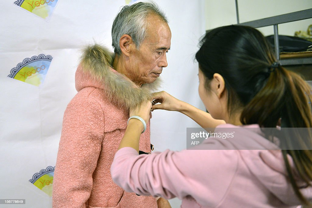 This picture taken on November 20, 2012 shows Liu Xianping (L) who is a 72 year old grandfather preparing to model women's clothing for his granddaughter's online fashion company 'Yecoo' in Guangzhou, south China's Guangdong province. Grandpa Liu who has become an internet sensation in China spent most of his life as a poor farmer in remote Hunan Province. AFP PHOTO CHINA OUT