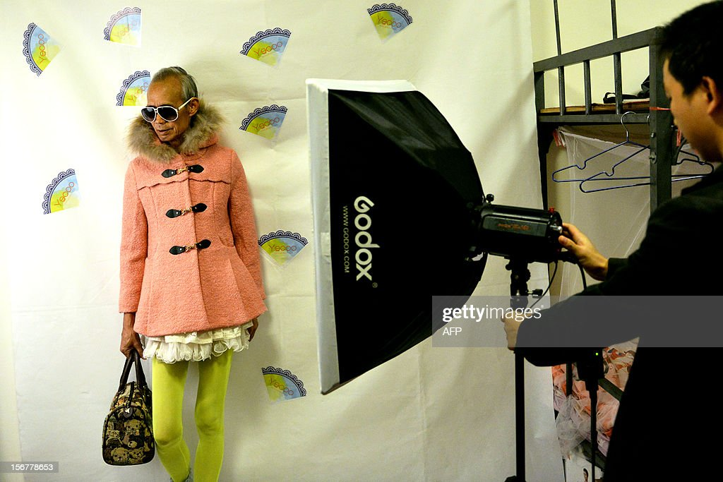 This picture taken on November 20, 2012 shows Liu Xianping (L) who is a 72 year old grandfather preparing to model women's clothing for his granddaughter's (L) online fashion company 'Yecoo' in Guangzhou, south China's Guangdong province. Grandpa Liu who has become an internet sensation in China spent most of his life as a poor farmer in remote Hunan Province. AFP PHOTO CHINA OUT