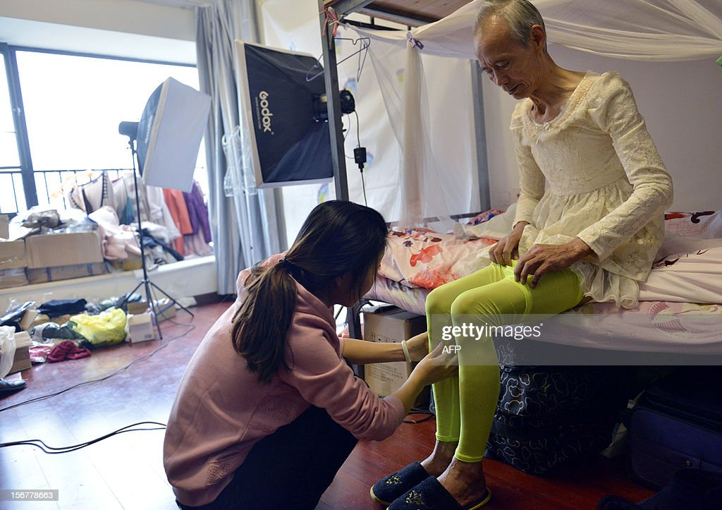 This picture taken on November 20, 2012 shows Liu Xianping (R) who is a 72 year old grandfather preparing to model women's clothing for his granddaughter's (L) online fashion company 'Yecoo' in Guangzhou, south China's Guangdong province. Grandpa Liu who has become an internet sensation in China spent most of his life as a poor farmer in remote Hunan Province. AFP PHOTO CHINA OUT