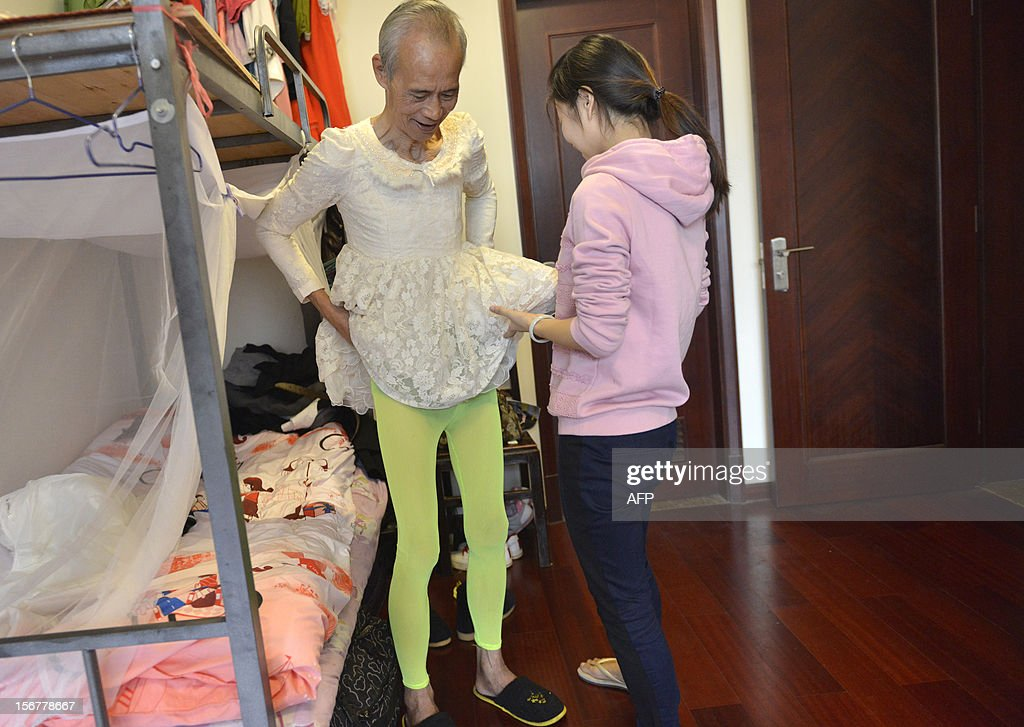 This picture taken on November 20, 2012 shows Liu Xianping (L) who is a 72 year old grandfather preparing to model women's clothing for his granddaughter's (R) online fashion company 'Yecoo' in Guangzhou, south China's Guangdong province. Grandpa Liu who has become an internet sensation in China spent most of his life as a poor farmer in remote Hunan Province. AFP PHOTO CHINA OUT