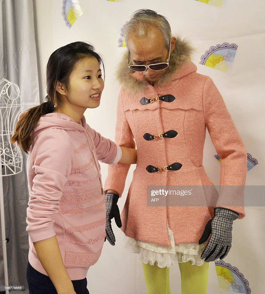 This picture taken on November 20, 2012 shows Liu Xianping (R) who is a 72 year old grandfather modeling women's clothing for his granddaughter's (L) online fashion company 'Yecoo' in Guangzhou, south China's Guangdong province. Grandpa Liu who has become an internet sensation in China spent most of his life as a poor farmer in remote Hunan Province. AFP PHOTO CHINA OUT
