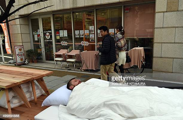 This picture taken on November 21 2015 shows a man looking at French artist Laurent Boijeot sleeping on furniture setup along a road in Tokyo After...
