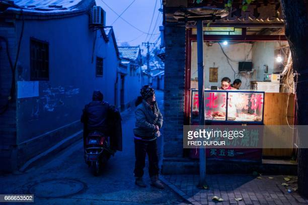 This picture taken on November 21 2016 shows a woman walking past a shop in a hutong in Beijing With space scarce in the city of 215 million most...