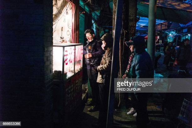 This picture taken on November 21 2016 shows people buy rice cakes in a hutong in Beijing With space scarce in the city of 215 million most hutong...