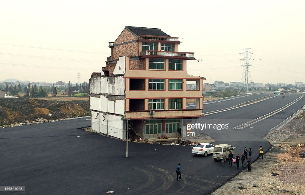 This picture taken on November 22, 2012 shows a half-demolished apartment building standing in the middle of a newly-built road thanks to a Chinese couple that refused to move in Wenling, in eastern China's Zhejiang province. Luo Baogen, 67, and his 65-year-old wife have waged a four-year battle to receive more than the 41,300 USD compensation offered by the local government of Daxi, a Chinese newspaper said. The phenomenon is called a 'nail house' in China, as such buildings stick out and are difficult to remove, like a stubborn nail. CHINA OUT AFP PHOTO