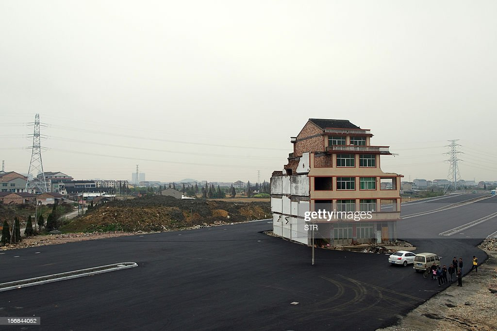 This picture taken on November 22, 2012 shows a half-demolished apartment building standing in the middle of a newly-built road thanks to a Chinese couple that refused to move in Wenling, in eastern China's Zhejiang province. Luo Baogen, 67, and his 65-year-old wife have waged a four-year battle to receive more than the 41,300 USD compensation offered by the local government of Daxi, a Chinese newspaper said. The phenomenon is called a 'nail house' in China, as such buildings stick out and are difficult to remove, like a stubborn nail. CHINA