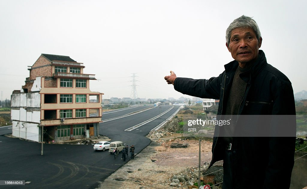 This picture taken on November 22, 2012 shows Luo Baogen pointing at his half-demolished apartment building that stands in the middle of a newly-built highway in Wenling, in eastern China's Zhejiang province. Luo Baogen, 67, and his 65-year-old wife have waged a four-year battle to receive more than the 41,300 USD compensation offered by the local government of Daxi, a Chinese newspaper said. The phenomenon is called a 'nail house' in China, as such buildings stick out and are difficult to remove, like a stubborn nail. CHINA OUT AFP PHOTO