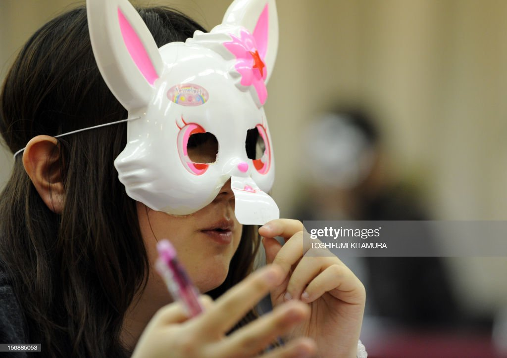 This picture taken on November 23, 2012 shows a 27-year-old woman wearing a rabbit mask introducing herself with her online name of 'Jet-Black Wings' speaks during a match-making party in Washinomiya, Saitama prefecture, in the northern suburbs of Tokyo. Self-confessed geeks in Japan who might ordinarily be too shy to ask someone on a date are trying a new kind of matchmaking: wearing cartoon character masks.
