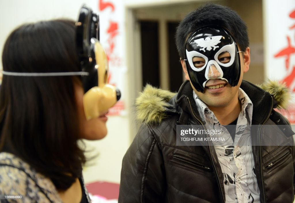 This picture taken on November 23, 2012 shows a 33-year-old man, who had introduced himself as Furuta Oribe from a historically famous tea master (R), speaking during an interview after being matched up with a Mickey Mouse masked woman (R) as they wear cartoon character masks during a match-making party in Washinomiya, Saitama prefecture, in the northern suburbs of Tokyo. Self-confessed geeks in Japan who might ordinarily be too shy to ask someone on a date are trying a new kind of matchmaking: wearing cartoon character masks. AFP PHOTO / TOSHIFUMI KITAMURA
