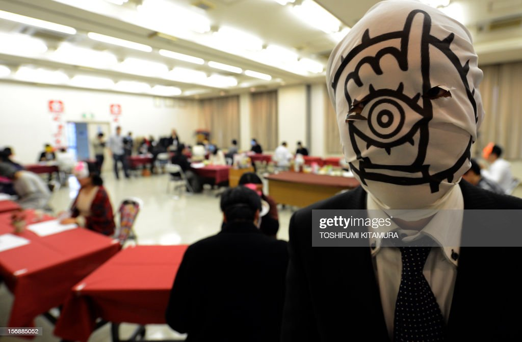 This picture taken on November 23, 2012 shows a ceremony master (R) posing with a 'Tomodachi' character mask during a match-making party in Washinomiya, Saitama prefecture, in the northern suburbs of Tokyo. Self-confessed geeks in Japan who might ordinarily be too shy to ask someone on a date are trying a new kind of matchmaking: wearing cartoon character masks. AFP PHOTO / TOSHIFUMI KITAMURA