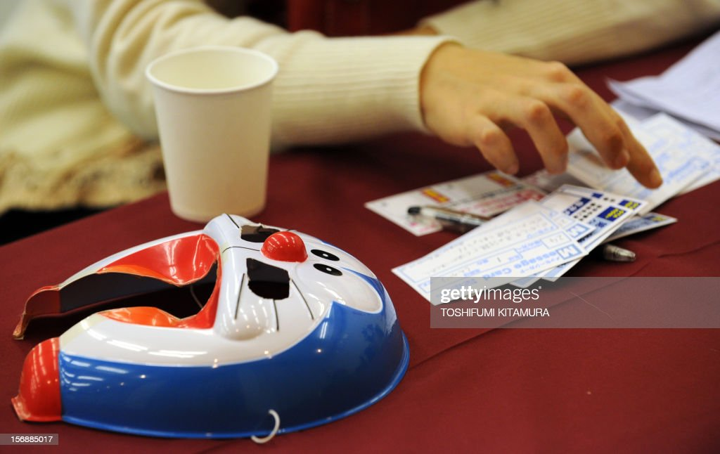 This picture taken on November 23, 2012 shows a female participant writing a message on a card next to a 'Doraemon' character mask, during a match-making party in Washinomiya, Saitama prefecture, in the northern suburbs of Tokyo. Self-confessed geeks in Japan who might ordinarily be too shy to ask someone on a date are trying a new kind of matchmaking: wearing cartoon character masks.