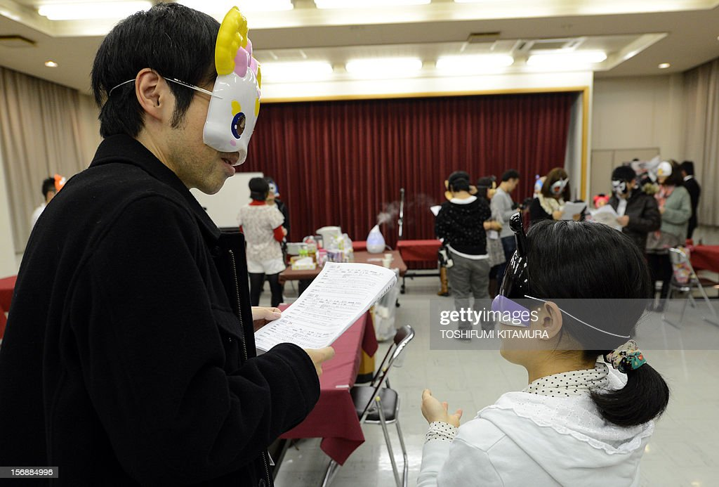 This picture taken on November 23, 2012 shows a man and a woman chatting as they wear cartoon character masks during a match-making party in Washinomiya, Saitama prefecture, in the northern suburbs of Tokyo. Self-confessed geeks in Japan who might ordinarily be too shy to ask someone on a date are trying a new kind of matchmaking: wearing cartoon character masks.