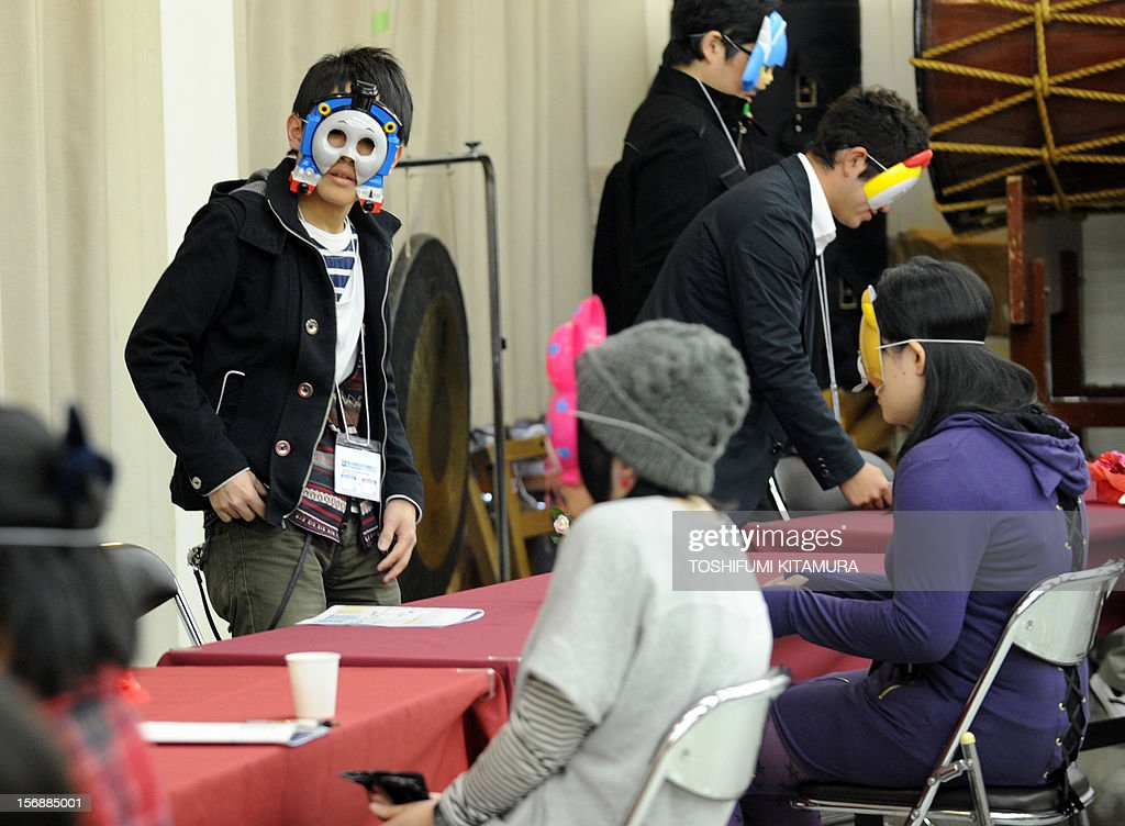 This picture taken on November 23, 2012 shows men taking their seats as they wear cartoon character masks during a match-making party in Washinomiya, Saitama prefecture, in the northern suburbs of Tokyo. Self-confessed geeks in Japan who might ordinarily be too shy to ask someone on a date are trying a new kind of matchmaking: wearing cartoon character masks.