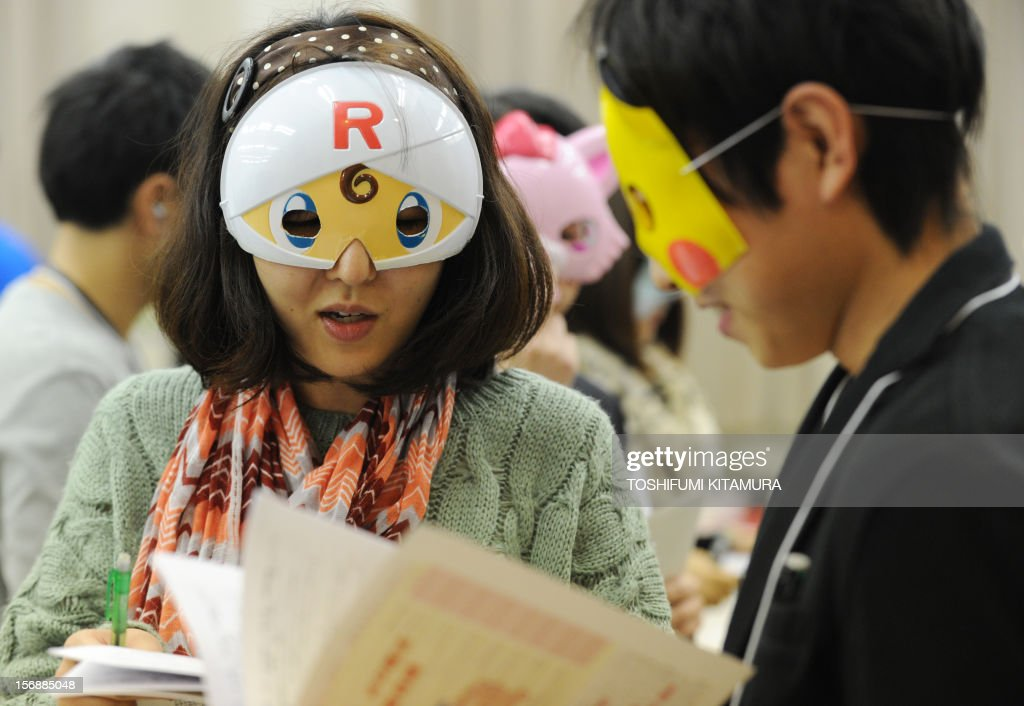 This picture taken on November 23, 2012 shows participants chatting as they wear cartoon character masks during a match-making party in Washinomiya, Saitama prefecture, in the northern suburbs of Tokyo. Self-confessed geeks in Japan who might ordinarily be too shy to ask someone on a date are trying a new kind of matchmaking: wearing cartoon character masks.