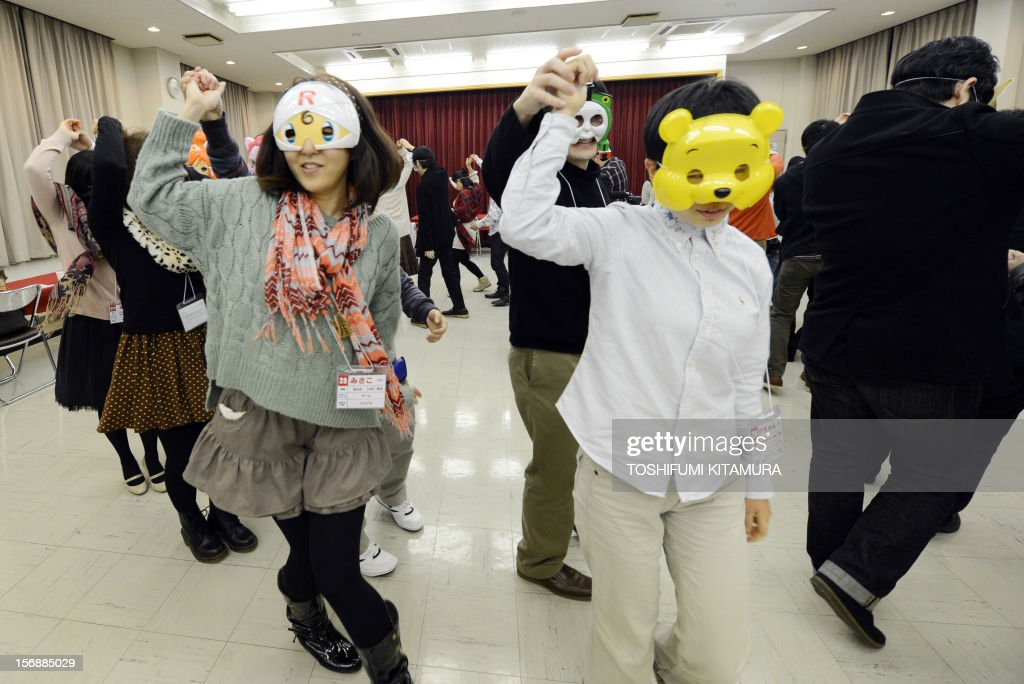 This picture taken on November 23, 2012 shows participants taking part in a folk dancing session during a match-making party in Washinomiya, Saitama prefecture, in the northern suburbs of Tokyo. Self-confessed geeks in Japan who might ordinarily be too shy to ask someone on a date are trying a new kind of matchmaking: wearing cartoon character masks. AFP PHOTO / TOSHIFUMI KITAMURA