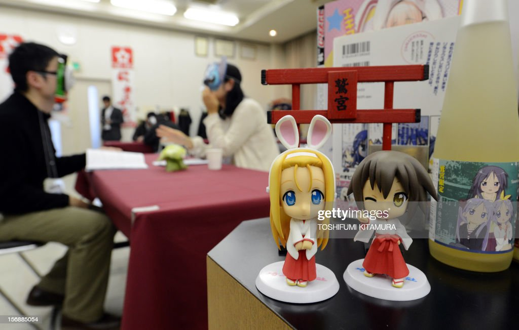 This picture taken on November 23, 2012 shows 'Raki-Suta' (Lucky Star) cartoon character dolls (R) displayed during a match-making party in Washinomiya, Saitama prefecture, in the northern suburbs of Tokyo. Self-confessed geeks in Japan who might ordinarily be too shy to ask someone on a date are trying a new kind of matchmaking: wearing cartoon character masks.