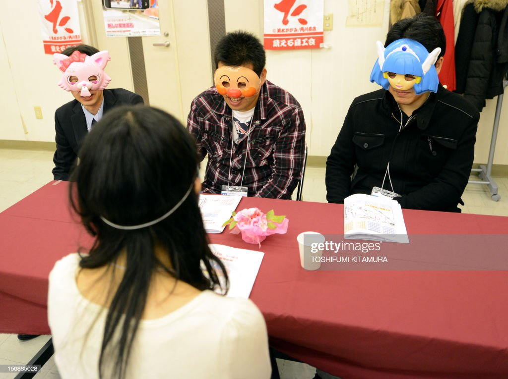 This picture taken on November 23, 2012 shows three men talking to a woman as they all wear masks during a match-making party in Washinomiya, Saitama prefecture, in the northern suburbs of Tokyo. Self-confessed geeks in Japan who might ordinarily be too shy to ask someone on a date are trying a new kind of matchmaking: wearing cartoon character masks. AFP PHOTO / TOSHIFUMI KITAMURA