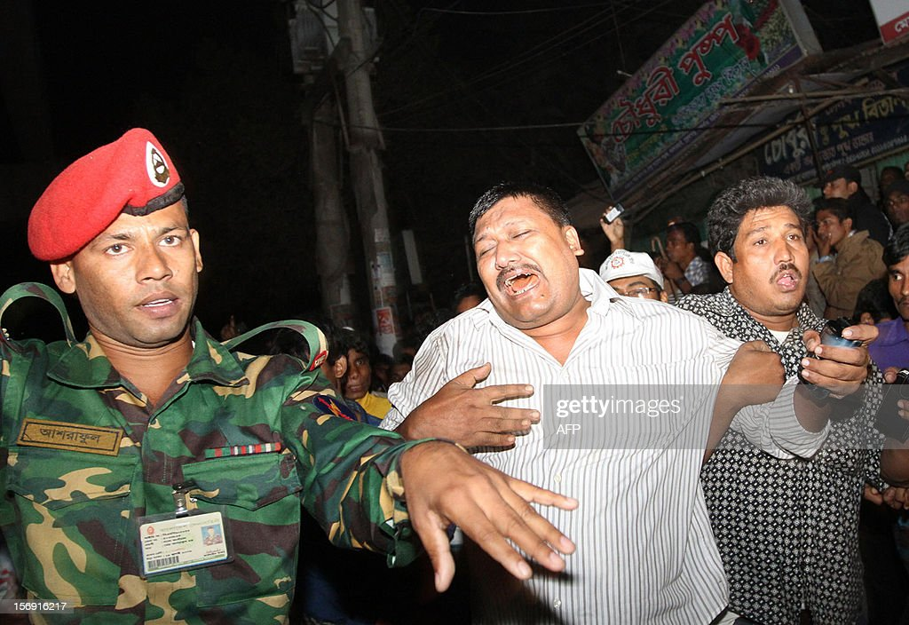 This picture taken on November 24, 2012 shows a man (C) mourning as he is supported by a man (R) after his relative was killed under the debris of three girders of an under-construction flyover in Chittagong. At least 13 people were killed and dozens are feared missing after a flyover under construction collapsed in Bangladesh's southeastern port city of Chittagong, police said on November 25. AFP PHOTO / Sowrav Das