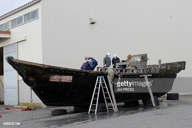 This picture taken on November 24 2015 shows coast guard officials investigating a wooden boat at the Fukui port in Sakai city in Fukui prefecture...