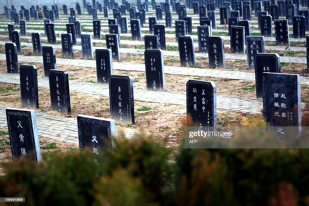 This picture taken on November 25, 2012 shows tombstones at a public cemetery that was built for the 'flatten graves to return farmland' campaign in suburb Zhoukou, central China's Henan province. Zhoukou has halted a campaign to clear graves for farmland after the demolition of more than two million tombs sparked outrage in a country where ancestors are traditionally held in deep respect. CHINA OUT AFP PHOTO