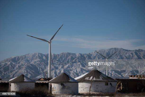 This picture taken on November 26 2015 shows wind turbines in Guanting outside of Beijing China is the world's biggest polluter and its emissions of...