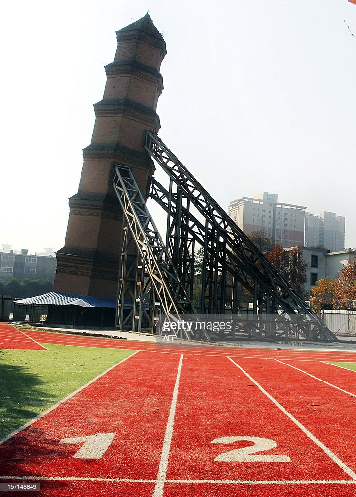 This picture taken on November 27, 2012 shows the Wanshou Temple Pagoda, built during China's Ming Dynasty (1368-1644), supported by steel frames at the Xiguang School in Xi'an, northwest China's Shaanxi province. Xi'an cultural heritage authorities are working on plans to set it upright after December 2012. CHINA