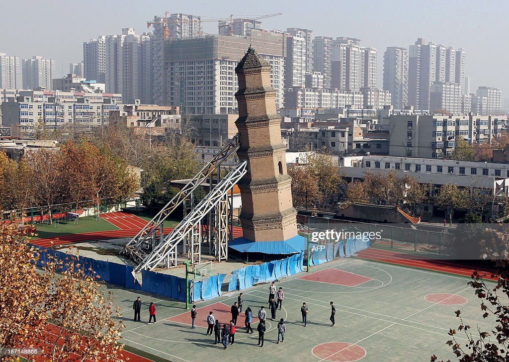 This picture taken on November 27, 2012 shows the Wanshou Temple Pagoda, built during China's Ming Dynasty (1368-1644), supported by steel frames at the Xiguang School in Xi'an, northwest China's Shaanxi province. Xi'an cultural heritage authorities are working on plans to set it upright after December 2012. CHINA OUT AFP PHOTO