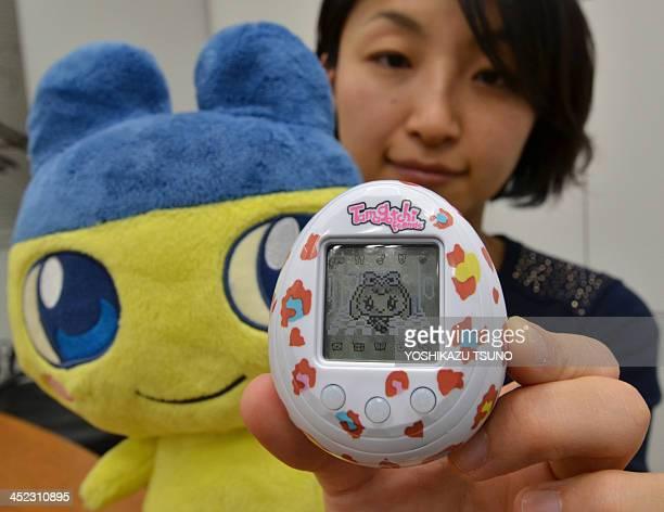 This picture taken on November 27 2013 shows Japanese toy giant Bandai employee Tomomi Washizu displaying the new Tamagotchi virtual pet toy release...