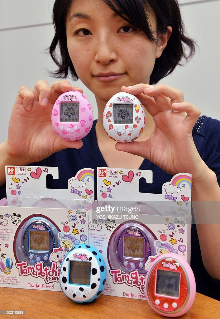 This picture taken on November 27, 2013 shows Japanese toy giant Bandai employee Tomomi Washizu displaying the new Tamagotchi virtual pet toy release 'Tamagotchi Friends', an egg-shaped portable toy featuring cartoonlike characters, at the company's headquarters in Tokyo. Tamagotchi, the egg-shaped virtual pet beloved of schoolchildren in the 1990s, is making a comeback and is set to hit the shelves of European shops in time for Christmas. AFP PHOTO / Yoshikazu TSUNO