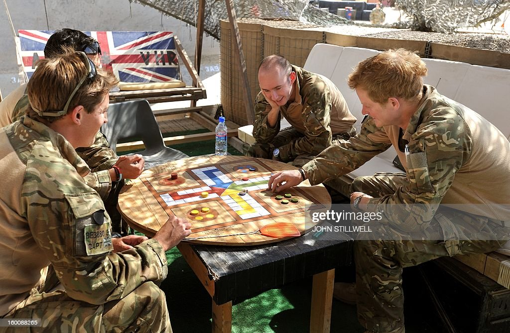 This picture taken on November 3, 2012 shows Britain's Prince Harry playing a game of Uckers in the VHR (very high ready-ness) tent with fellow pilots at Camp Bastion in Afghanistan's Helmand province. Prince Harry said he was 'thrilled to be back' in Britain as he returned home after serving a 20-week tour of duty in Afghanistan. The 28-year-old Apache attack helicopter co-pilot arrived back on home turf after spending two days' mandatory post-deployment 'decompression' time at a British base in Cyprus. AFP PHOTO/POOL/John STILLWELL - NOTE