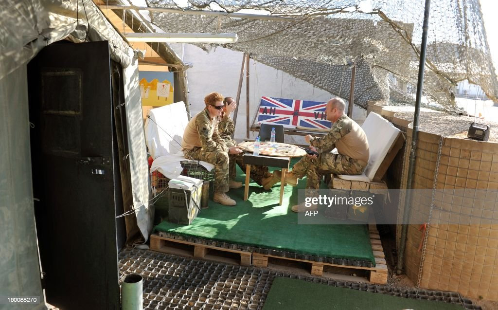 This picture taken on November 3 2012 shows Britain's Prince Harry playing a game of Uckers in the VHR tent with fellow pilots at Camp Bastion in...