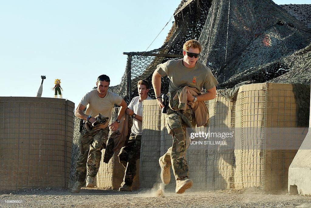 This picture taken on November 3 2012 shows Britain's Prince Harry running out from the VHR tent to scramble his Apache helecopter with fellow Pilots...