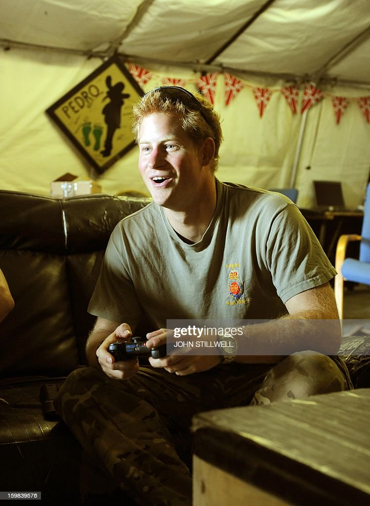 This picture taken on November 3, 2012 shows Britain's Prince Harry (R) playing computer games in the VHR (very high ready-ness) at the British controlled flight-line at Camp Bastion in Afghanistan's Helmand Province, where he was serving as an Apache Helicopter Pilot/Gunner with 662 Sqd Army Air Corps. Britain's Prince Harry confirmed he killed Taliban fighters during his stint as a helicopter gunner in Afghanistan, it can be reported after he completed his tour of duty on January 21, 2013.