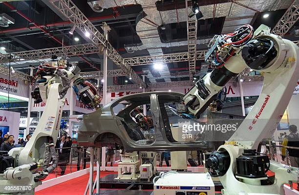 This picture taken on November 3 2015 shows visitors watching robots welding a car at the 17th China International Industry Fair in Shanghai The fair...