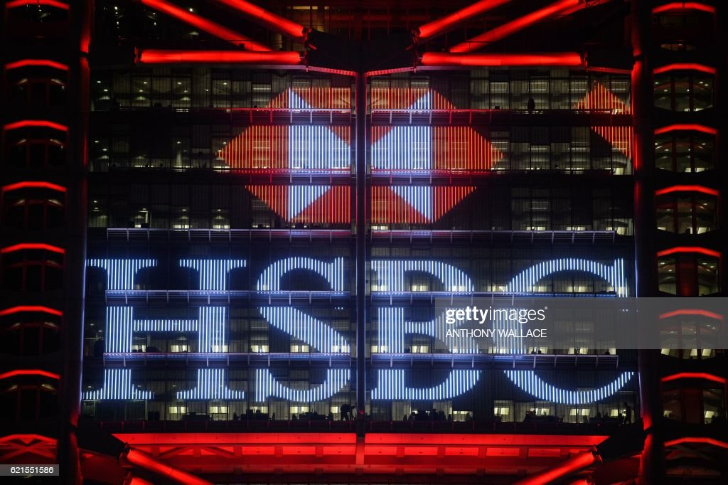 This picture taken on November 4, 2016 shows the illuminated HSBC logo at night on the facade of the HSBC headquarters building in Hong Kong. HSBC said on November 7 its third quarter adjusted pretax profit rose seven percent from a year ago to USD 5.59 billion, beating expectations. / AFP / ANTHONY