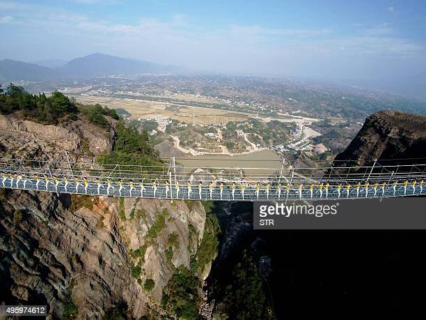 This picture taken on November 5 2015 shows Chinese yoga fans performing on a glassbottomed suspension bridge in the Shiniuzhai mountains in...